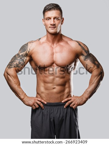 Muscular man with tattos posing in studio