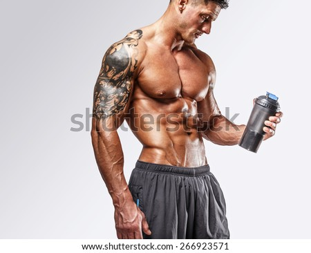 Muscular man with tattos posing in studio - stock photo