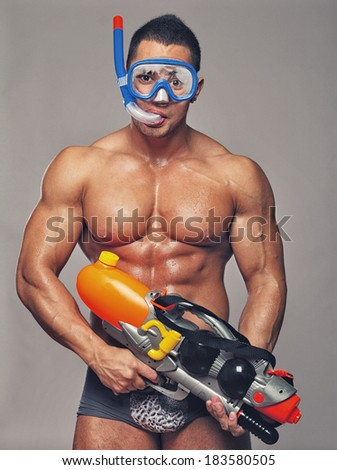 muscular man with water gun and with swimming equipments - stock photo