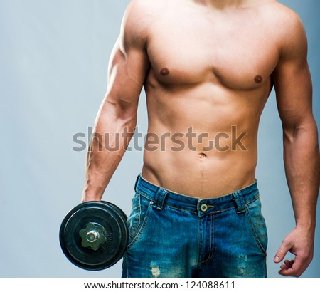 Muscular man with weights on a gray background - stock photo
