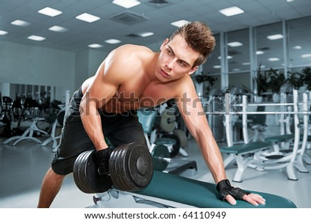 Muscular man working his biceps with heavy dumbbells - stock photo