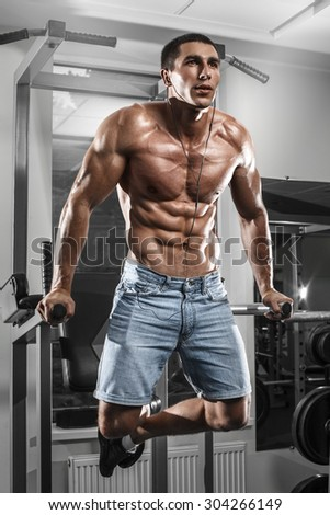 Muscular man working out in gym doing exercises on parallel bars, strong male naked torso abs - stock photo