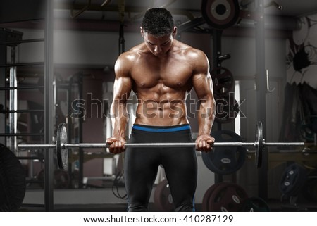Muscular man working out in gym doing exercises with barbell at biceps, strong male naked torso abs - stock photo