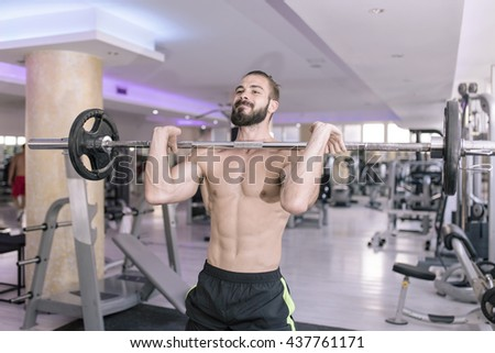 Muscular man working out in gym doing exercises with barbell for biceps, strong male naked torso abs - stock photo