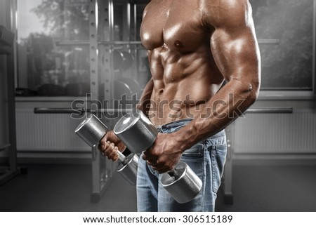 Muscular man working out in gym doing exercises with dumbbells, strong male naked torso abs - stock photo