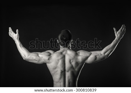 Muscular man working out with weights in gym. Man makes exercises.