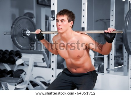 Muscular man working  with heavy rod