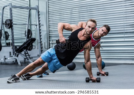 Muscular men doing a side plank while lifting a dumbbell - stock photo