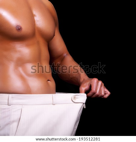 Muscular men showing how much weight he lost. Professional studio lighting. Isolated on black background - stock photo