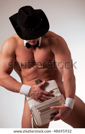 Muscular naked male stripper with purse - stock photo