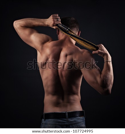 muscular naked man from back on black - stock photo