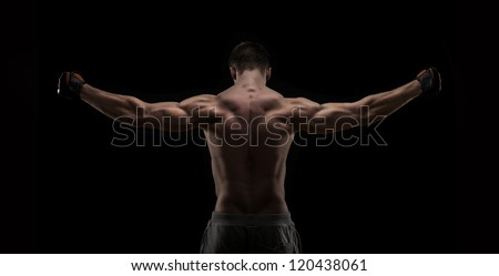 Muscular naked man from back on black background - stock photo