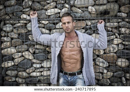 Muscular sexy man in front of stone wall, naked torso under knitted sweater, looking at camera - stock photo