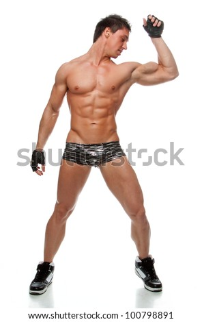 Muscular sexy naked man dancing in the studio in underwear, shoes and gloves