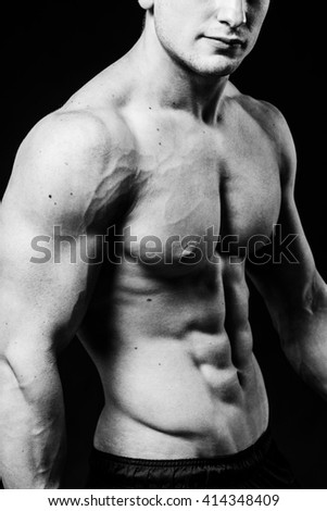 Muscular sexy torso of young sporty man with perfect abs close up. Black and white isolated on black background - stock photo