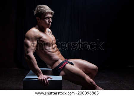 Muscular sexy young wet naked guy sitting - stock photo
