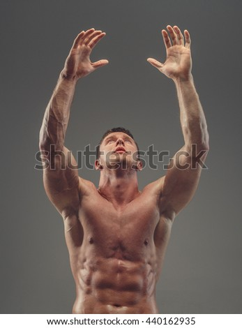 Muscular shirtless athlete isolated on a grey background.