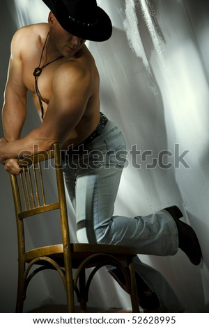 Muscular shirtless cowboy leaning on chair against a white wall - stock photo