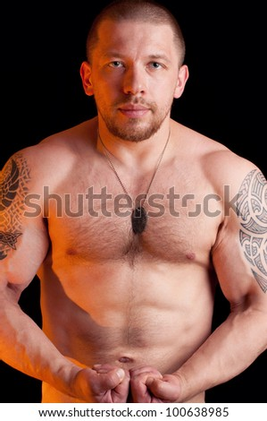 Muscular shirtless male with dog tags posing over black background