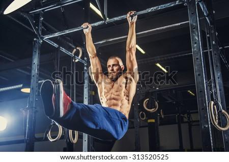 Muscular shirtless man doing pulling up on horizontal bar. - stock photo
