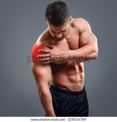 Muscular shirtless man with shoulder pain over gray background. Concept with highlighted glowing red spot. - stock photo