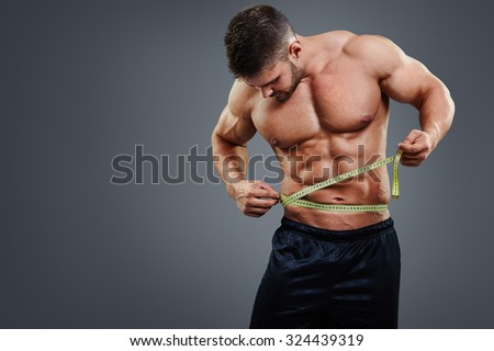 Muscular sports man measuring his waist with tape measure isolated over gray background. Bodybuilder waist measure concept.