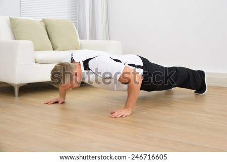 Muscular Sporty Man Doing Pushups In A Living Room - stock photo