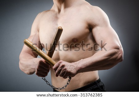 Muscular strong man with nunchucks  - stock photo