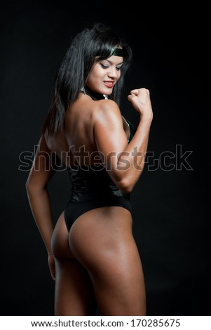 Muscular strong woman posing against black background