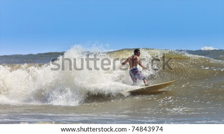 muscular surfer catching a wave on the atlantic - stock photo