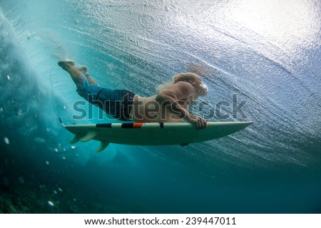 muscular surfer with long white hair riding on big waves on the Indian Ocean island of Mauritius, picture was taken under water