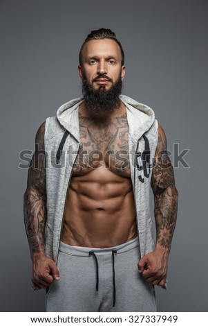 Muscular tattooed man with beard in grey zipuo hoodies. Isolated on grey background. - stock photo