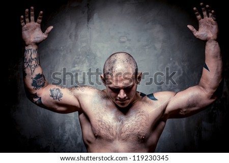 Muscular tattooed man with hands raised up posing over grey background - stock photo
