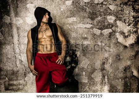 Muscular thug leaning against dirty grungy wall looking to a side at large copyspace - stock photo