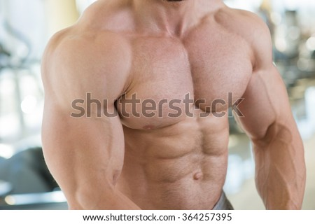 Muscular torso and arms. Bodybuilder with huge muscles. Strong manâ??s torso. Picture of muscular torso, arms and abs. - stock photo