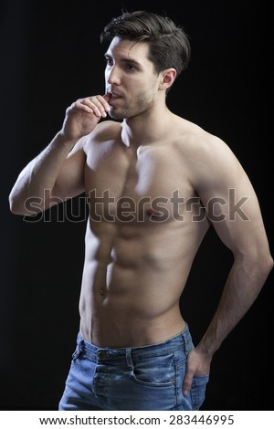muscular torso of man on black background - stock photo