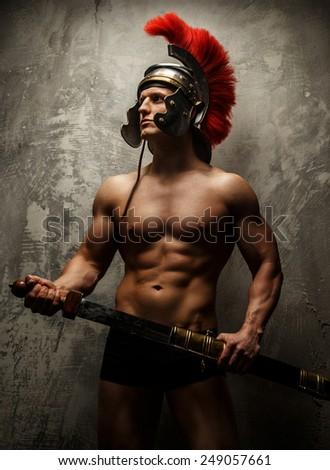 Muscular warrior with sword and helmet posing - stock photo