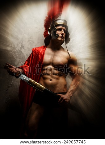 Muscular warrior with sword and helmet posing in front of concrete wall