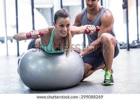 Muscular woman balancing while lifting dumbbells - stock photo
