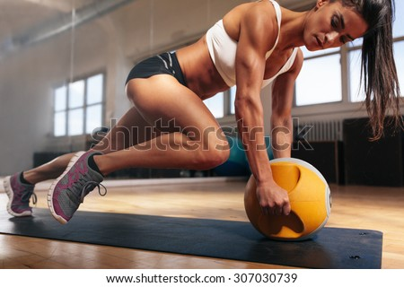 Muscular woman doing intense core workout in gym. Strong female doing core exercise on fitness mat with medicine ball in health club. - stock photo