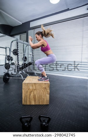 Muscular woman doing jumping squats on a wooden box - stock photo