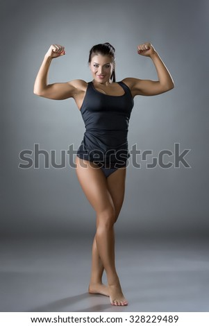 Muscular woman posing in studio, on gray backdrop - stock photo