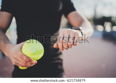 Muscular young athlete checking heart rate and calories on his smartphone application after good workout outdoor session on sunny park.Blurred background