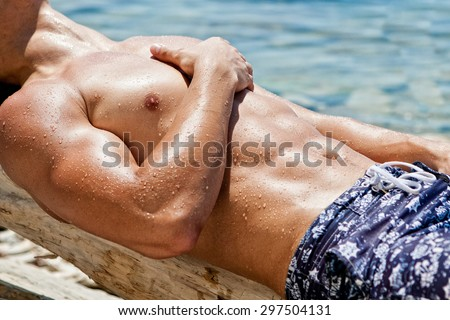 Muscular young athletic sexy man lying on the beach with a naked torso in underwear - stock photo