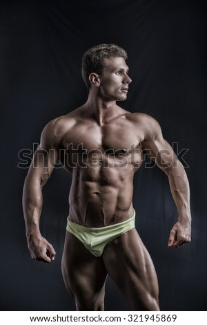 Muscular young bodybuilder in relaxed pose, looking to a side. On dark background, wearing underwear - stock photo