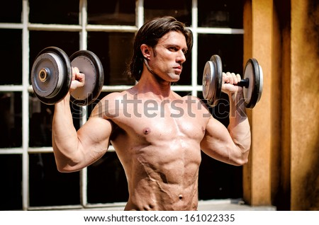 Muscular young bodybuilder shirtless outdoors, exercising biceps with dumbbells - stock photo