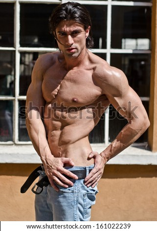 Muscular young bodybuilder shirtless outdoors in jeans, undressing - stock photo