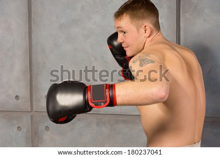 Muscular young boxer facing off with his fist raised to protect his head as he seeks on opening for a punch, close up side view - stock photo