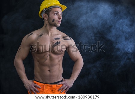 Muscular young construction worker shirtless wearing hardhat, dark background with smoke - stock photo