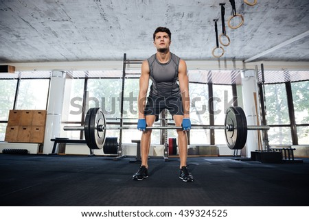 Muscular young fitness man workout with barbell in fitness gym - stock photo